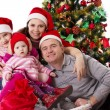 family with two little daughters under chritmas tree — Stock Photo