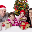 Family with two little daughters lying under Christmas tree — Stok fotoğraf