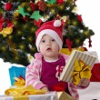 Little girl in Santa hat sitting under Christmas tree — Stock Photo