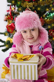 Girl in pink fur hat holding present under Chritmas tree — Stock Photo