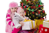 Sisters sitting with gifts under Christmas tree — Stock Photo