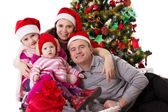 Family with two little daughters under Chritmas tree — Stok fotoğraf