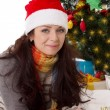 Woman in Santa hat and fur mittens lying under Christmas tree — Stock Photo #36578463