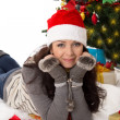 Woman in Santa hat and fur mittens lying under Christmas tree — Stock Photo #36578433