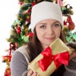 Woman in fur hat and mitten holding Christmas present — Stok fotoğraf