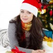 Woman in Santa hat lying under Christmas tree — Стоковая фотография