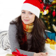Woman in Santa hat lying under Christmas tree — 图库照片