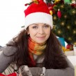 Woman in Santa hat and fur mittens lying under Christmas tree — Stock Photo