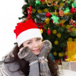 Woman in Santa hat and fur mittens lying under Christmas tree — Stock Photo #36578469