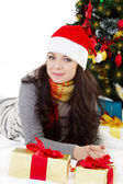 Woman in Santa hat lying under Christmas tree — Stock Photo