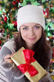 Woman in fur hat and mitten holding Christmas present — Stock Photo
