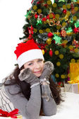 Woman in Santa hat and fur mittens lying under Christmas tree — Stockfoto
