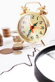 Magnifying glass, clock with coins — Stock Photo