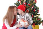 Mother and son under Christmas tree — Stok fotoğraf