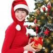 Smiling woman in red Santa hatunder Christmas tree — Stock Photo