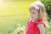 Baby girl among rapeseed field with camomile bouquet — Stock Photo