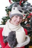 Woman in knitted hat and mitten under Christmas tree with cup — Stok fotoğraf