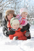 Mother with two children lying in snow — Stockfoto