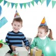 Two children at blue party table openning present — Stock Photo