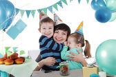 Two children hugging their mother at party table — Stock Photo