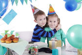 Two children huging at blue party table — Stock Photo