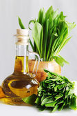 Fresh wild garlic leaves with mortar and oil — Stock Photo