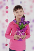Cute girl with violet tulip bouquet — Стоковое фото