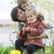 Mother and two children hugging among blooming garden — Stock Photo