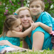 Mother and two children hugging among green grass — Stock Photo