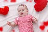 Baby girl with red plush hearts lying — Stock Photo