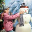 Stock Photo: Girl with a snowman on the background of a winter landscape