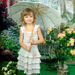 Beautiful girl with an umbrella in the openwork knit dress on gr — Stock Photo