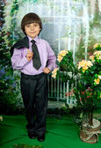 Cute boy in business suit and purple shirt around flowering shru — Stock Photo