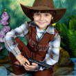 Royalty-Free Stock Photo: Cute little boy dressed as a cowboy with a gun on a green backgr