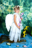 Sad girl with angel wings with pink orchids — Stock Photo