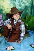 Söt liten pojke klädd som en cowboy med en pistol på en grön bakgrunds — Stockfoto
