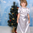 Cute girl in a silver dress around Christmas tree — Stock Photo #4338116