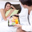 Young man serving breakfast for his girlfriend — Stock Photo #12297779