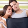 Couple lying in bed with laptop smiling — Stock Photo