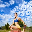 Young woman stretching before running — Stock Photo