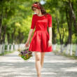 Stock Photo: Woman walking with flowers basket