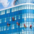 Stock Photo: Workers washing windows in the office building