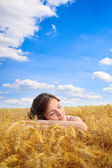 Pretty woman on yellow wheat field — Stockfoto