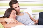 Uśmiechnięta para przy pomocy pewien laptop leżący na swoim łóżku — Zdjęcie stockowe