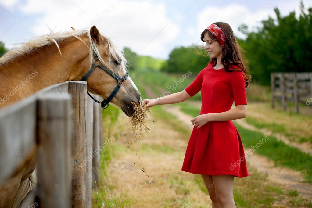 Young cute woman feeding horse on farm — Stock Photo #12630942