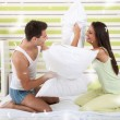 Happy couple playing with pillows in bed — Stok fotoğraf