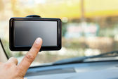 Finger pointing at car GPS — Stock Photo