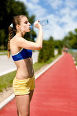 Sporty woman drinking water — Stock Photo