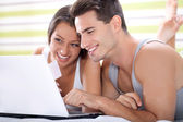 Couple shopping in bed — Stock Photo
