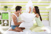 Happy couple playing with pillows in bed — Stock Photo